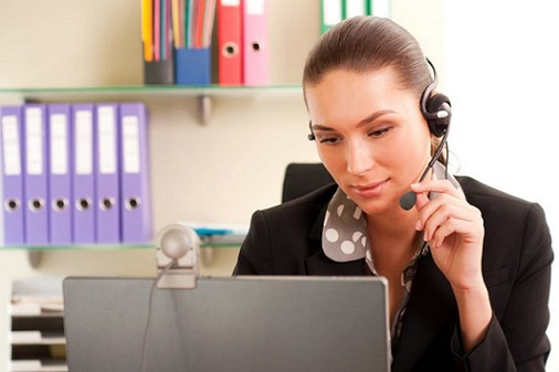 Young business woman working on computer and wearing headphones